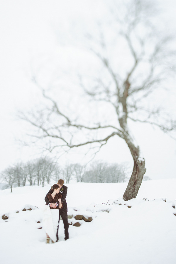 Bride and groom by tree in snow in Wisconsin