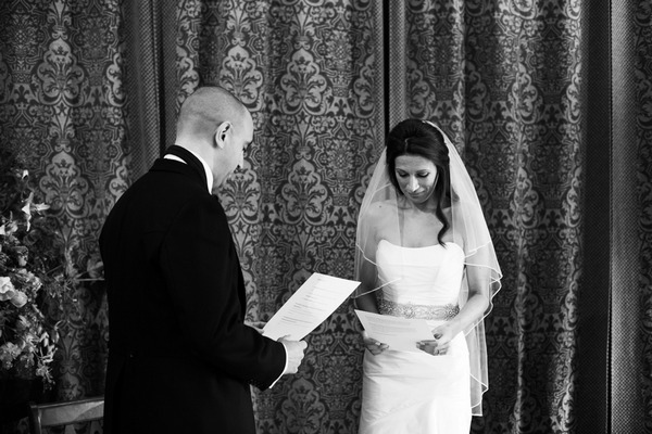 Bride and groom reading wedding vows