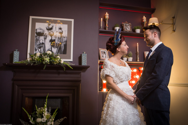 Bride and groom by fireplace at The Alverton Hotel