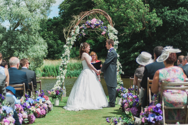 Wedding ceremony by lake at Narborough Hall Gardens