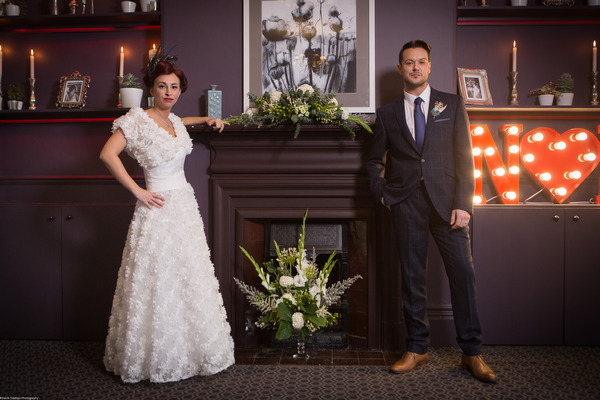Bride and groom standing by fireplace at The Alverton Hotel