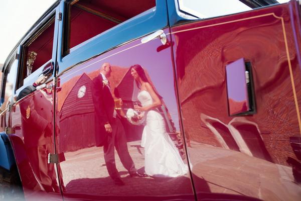 Reflection of bride and groom in door of wedding car