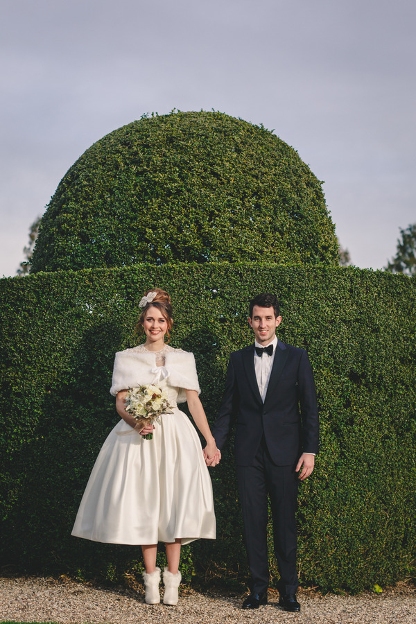 Bride and groom standing up against hedge
