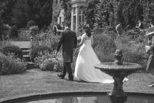 Bride and groom walking past fountain at Narborough Hall Gardens