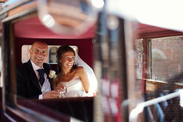 Bride and groom in back of wedding car