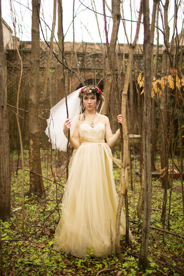 Bride standing in woodland