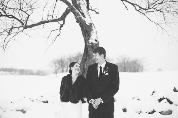 Bride and groom standing under tree in snow