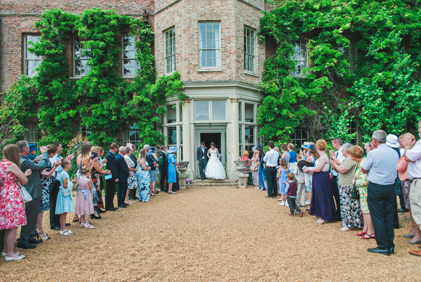 Bride and groom walking out of Narborough Hall