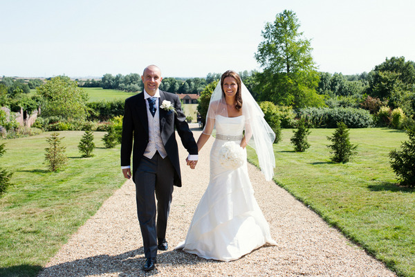 Bride and groom walking up Layer Marney Tower driveway