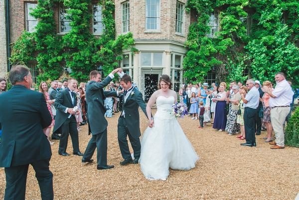 Groomsman throwing confetti over groom