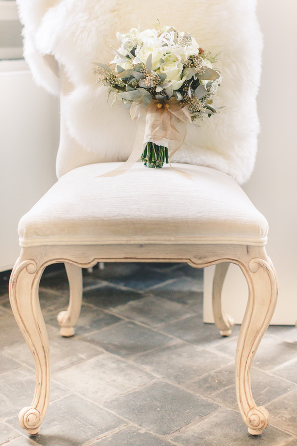 Elegant chair with wedding bouquet on seat