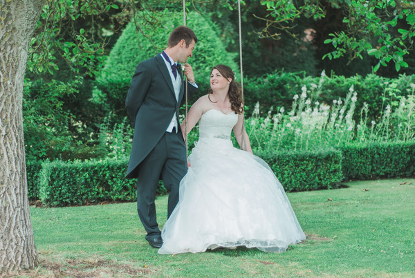 Bride and groom on swing at Narborough Hall Gardens