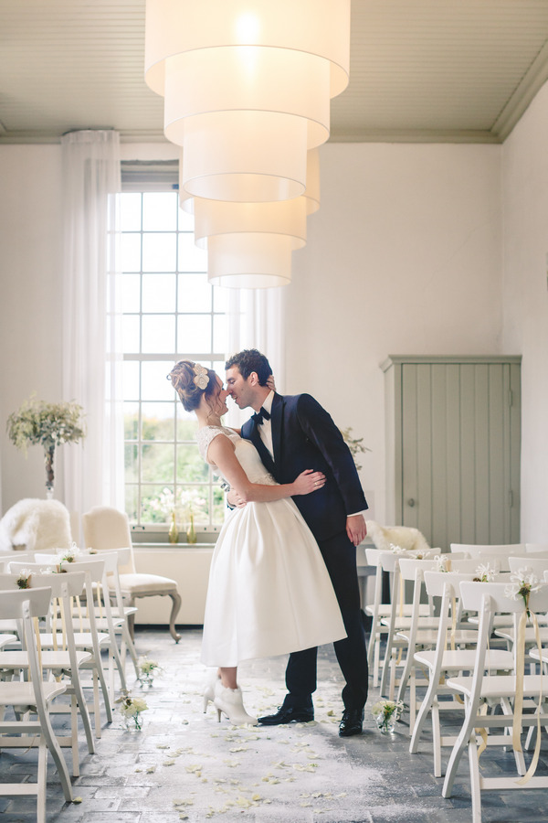 Bride and groom about to kiss in wedding ceremony room
