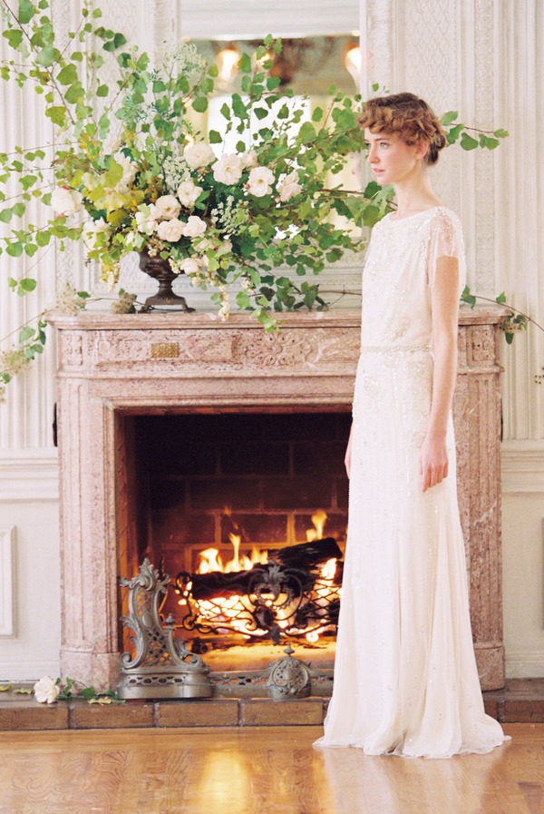 Bride standing by fireplace