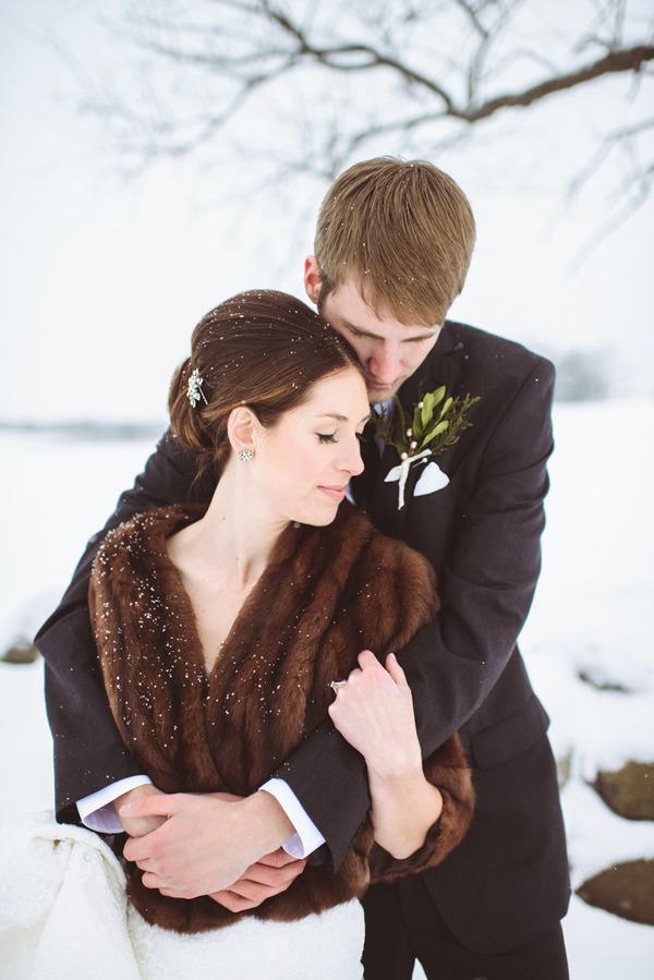 Groom hugging bride from behind in snow