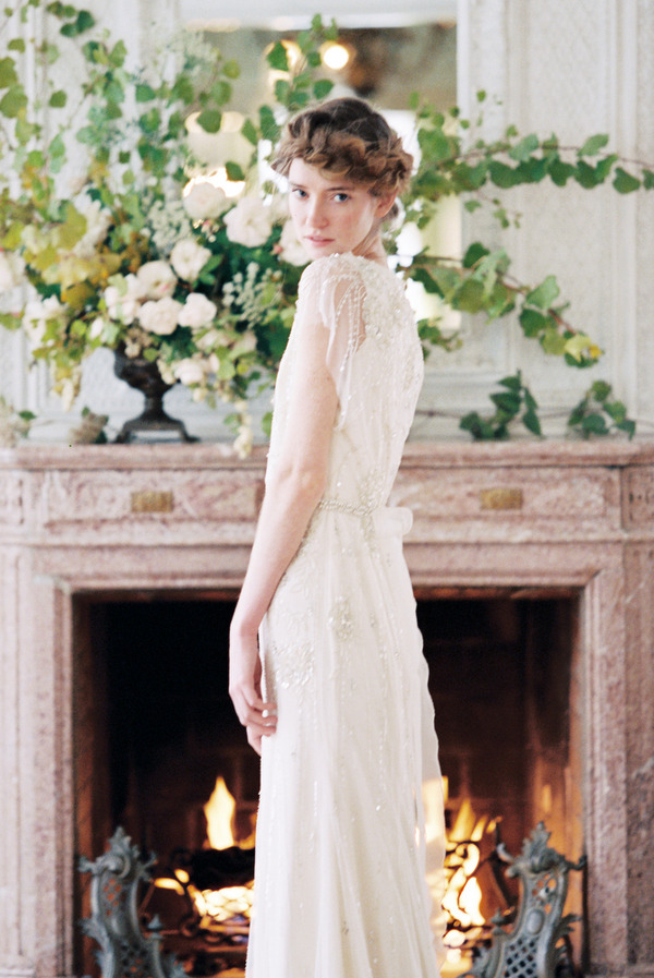 Bride standing in front of fireplace looking over shoulder