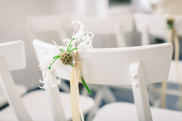 Small flower tied to back of wedding chair