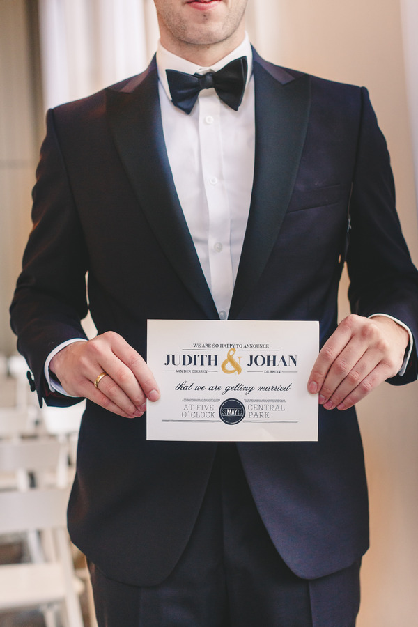 Groom holding wedding invitation