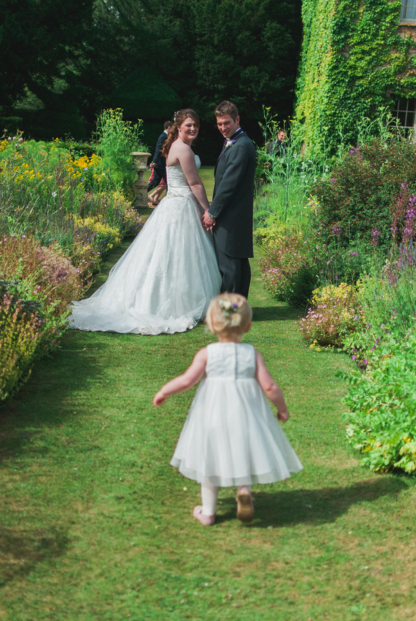 Flower girl running to bride and groom