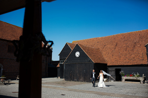 Bride and groom walking across courtyard of Layer Marney Tower