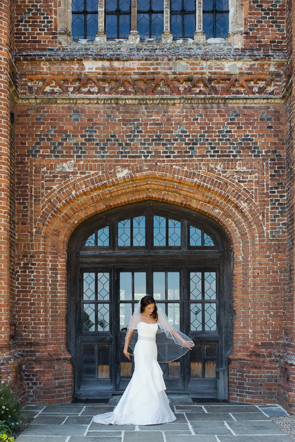 Bride standing in front of window at Layer Marney Tower