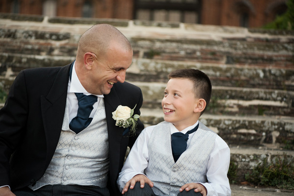 Groom sitting on steps of Layer Marney Tower with pageboy
