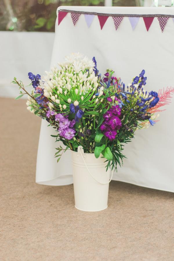 Purple flowers by wedding table
