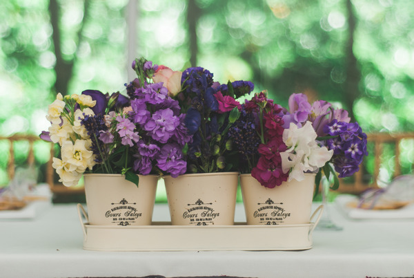 Purple flowers in pots on wedding table