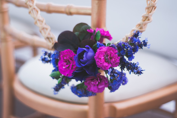 Purple and pink flowers tied to wedding chair