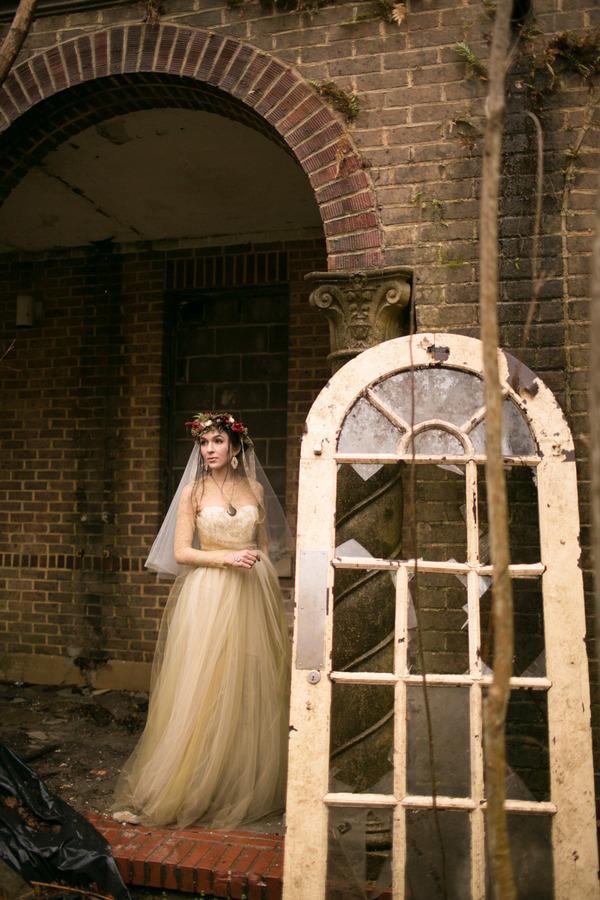 Bride standing by old broken window