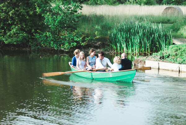 Wedding guests on rowing boat on lake at Narborough Hall Gardens