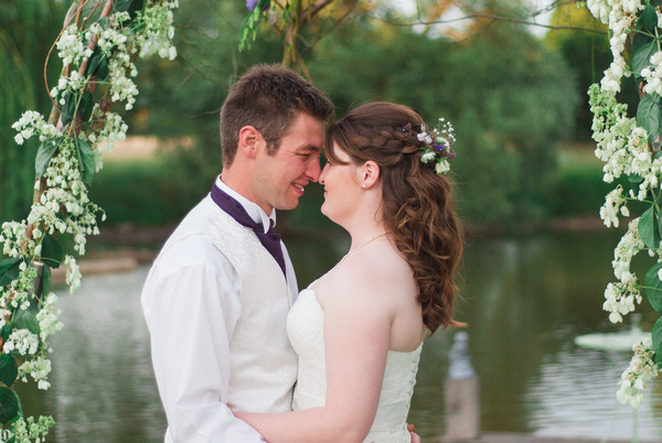 Bride and groom by lake at Narborough Hall Gardens
