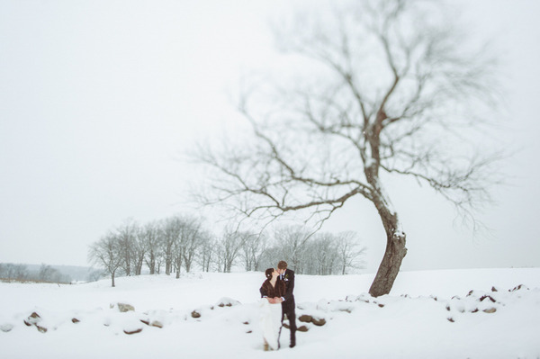 Bride and groom standing in snow in Wisconsin