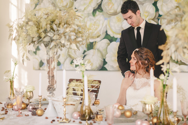 Bride sitting at wedding table with groom standing behind