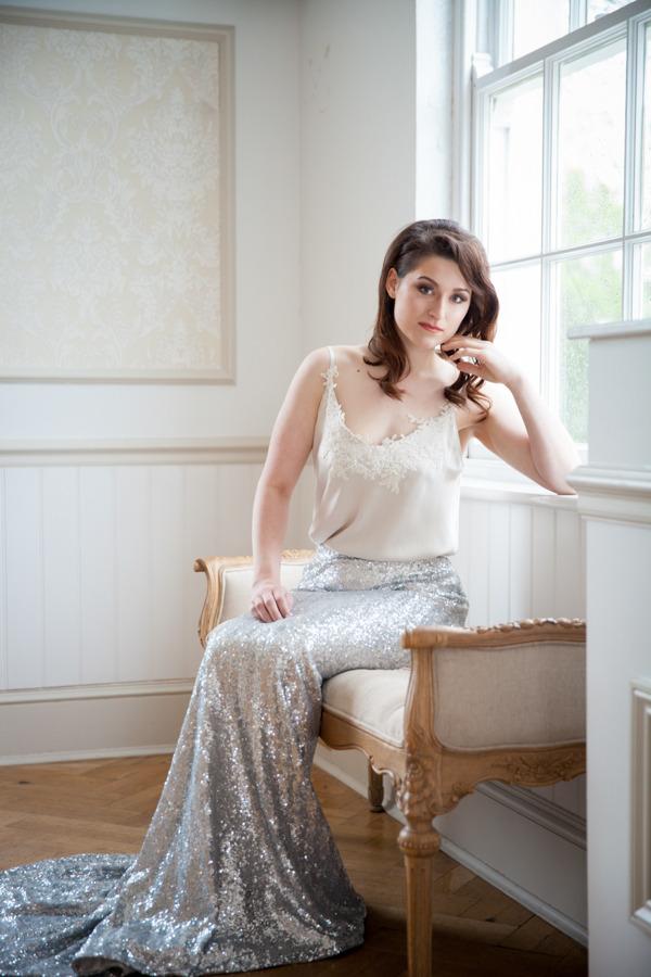 Bride in glittery silver skirt sitting by window