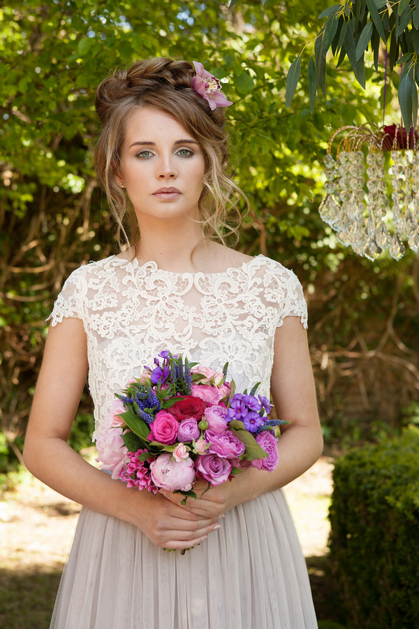 Bride with lace detail wedding dress holding bridal bouquet