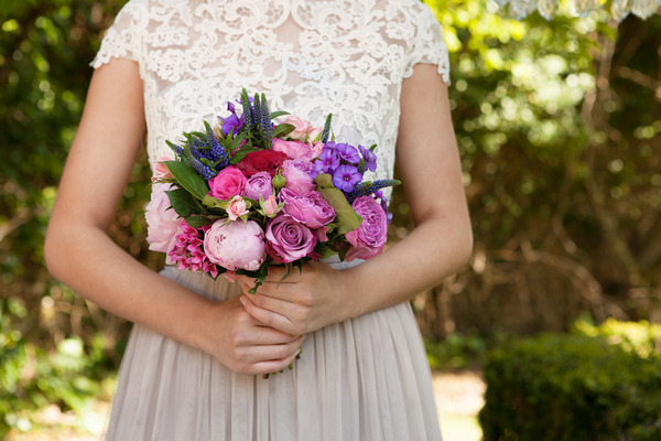 Bride holding pink and purple wedding bouquet