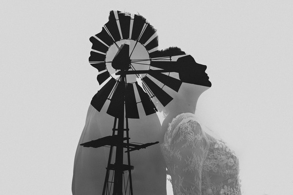 Bride and groom standing back to back with image of windmill overlayed for double exposure - Estefania Romero Photography