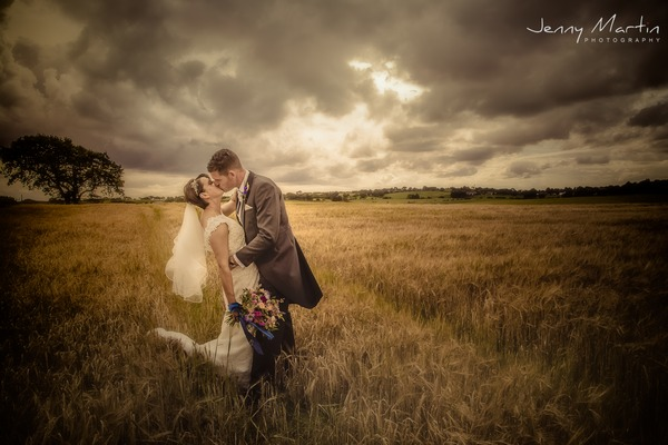 Bride and groom kissing in a field with dark clouds overhead - Picture by Jenny Martin Photography