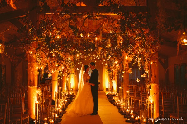 Bride and groom standing in orange lit ceremony room surrounded by candles and decorations - Picture by Jonny Draper Photography