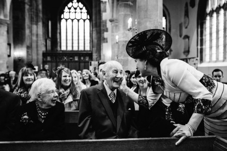 Lady wedding guest touching smiling elderly man's face before wedding ceremony - Picture by How Photography