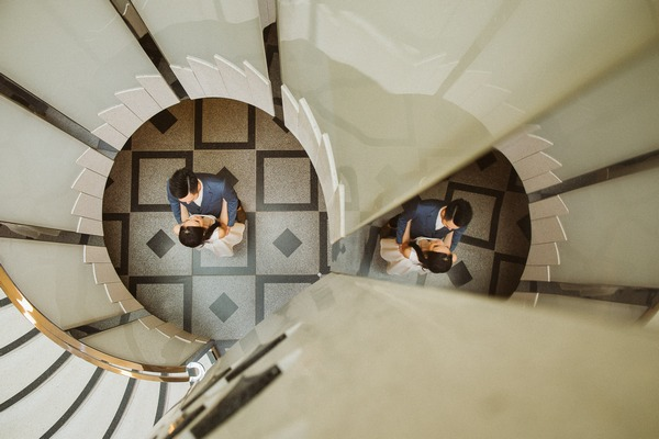 Bride and groom at bottom of spiral staircase with reflection in mirror - Picture by Voyteck Photography