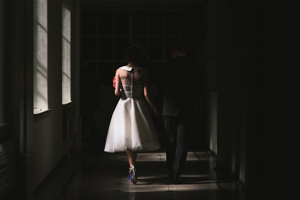 Bride and groom walking down dark corridor - Picture by Kristian Leven Photography