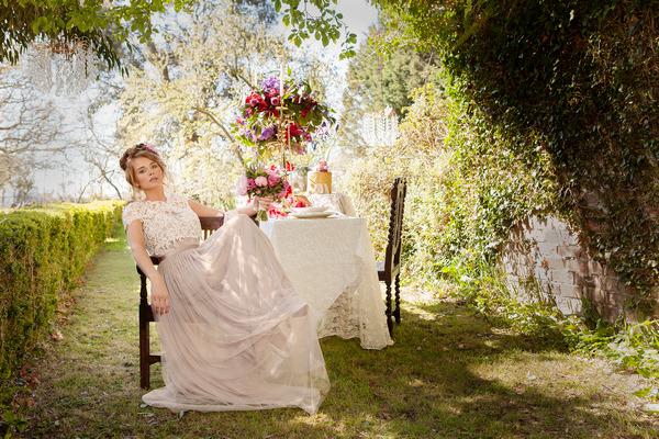 Bride sitting back in chair in garden of Tros Yr Afon