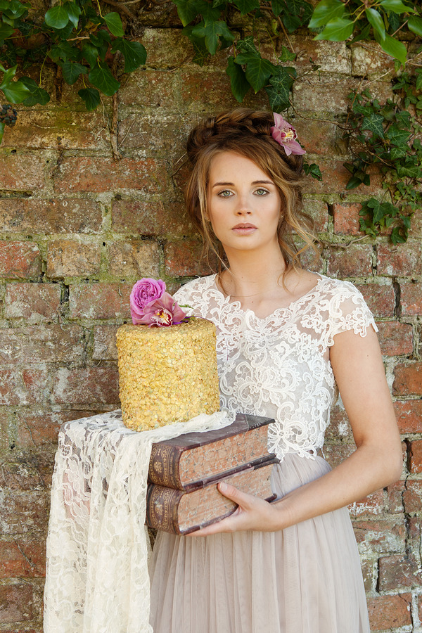 Bride holding wedding cake standing next to wall