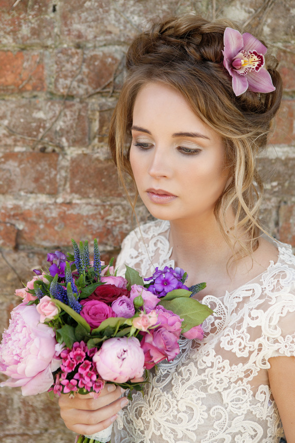 Bride with updo holding bouquet