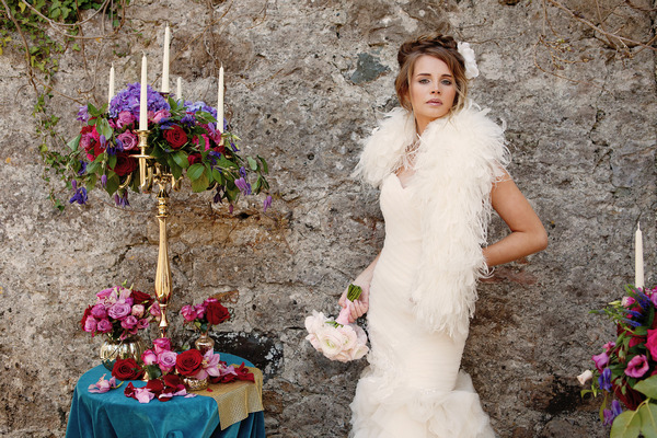Bride with long dress and shrug standing next to small table
