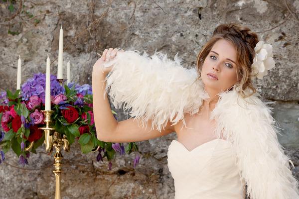 Bride holding shrug over shoulder