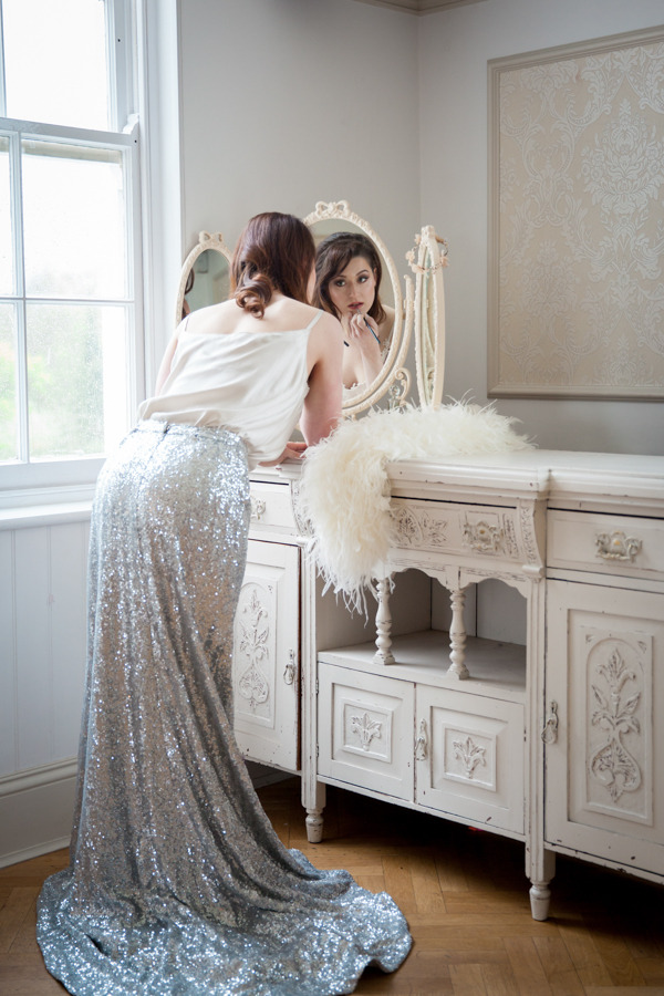 Bride in glittery silver skirt doing make-up in mirror