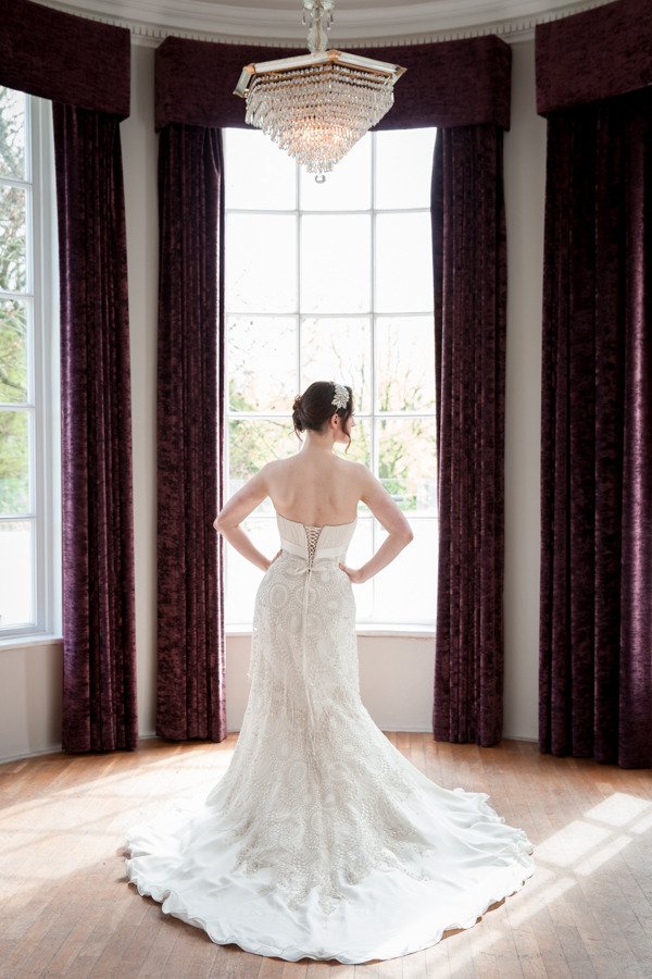 Bride with hands on hips show detail on back of wedding dress
